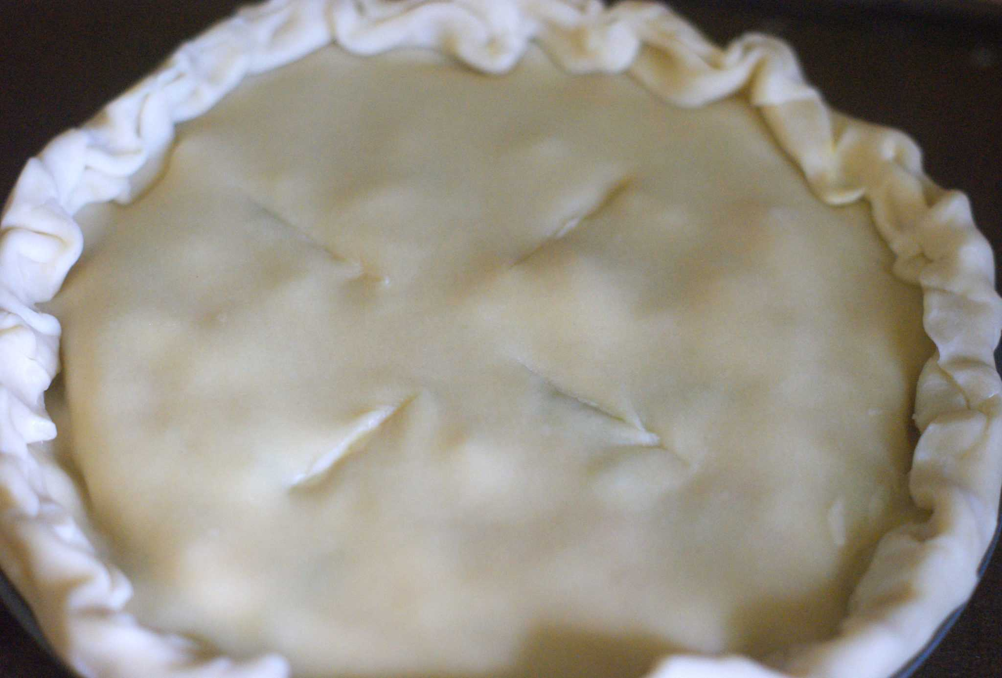 Uncooked chicken pot pie with pie crust