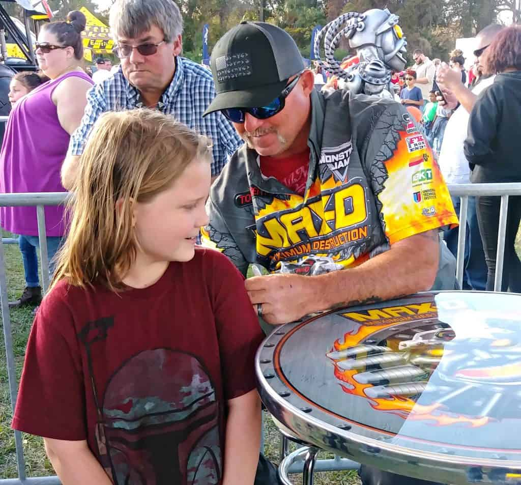 Max D Monster Truck Driver autographing a shirt at the pit party