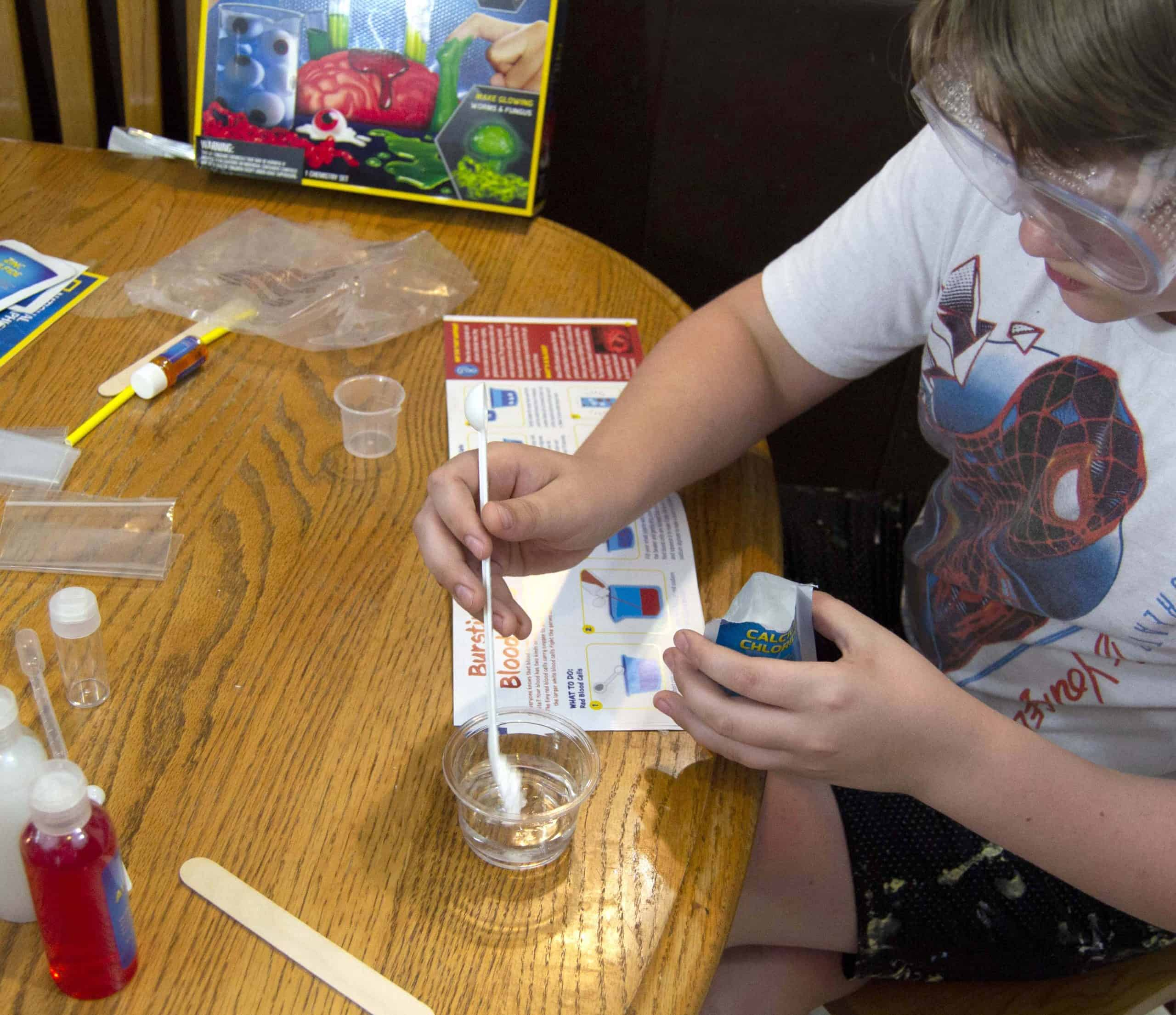 Boy doing science experiment using gross science kit
